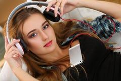 Die schöne blonde lächelnde Frau, die an gesetzt wird oder, entfernen Kopfhörer Stockbilder