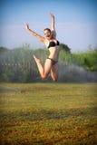 Die schöne Blondine in einem Badeanzugspringen Stockfotos