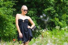 Die schöne Blondine in einem schwarzen Kleid Stockbild