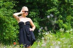 Die schöne Blondine in einem schwarzen Kleid Stockfotos