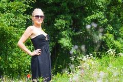 Die schöne Blondine in einem schwarzen Kleid Lizenzfreie Stockbilder