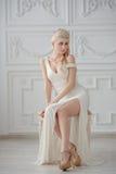 Die schöne Blondine in einem weißen Kleid auf Hintergrund Lizenzfreie Stockfotografie