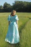 Die schöne Blondine in einem Weinlesekleid geht, zurück zu Kamera Stockfotografie
