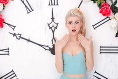 Die schöne Blondine im Hintergrund der großen Uhr stockfotografie