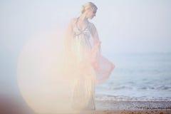 Die schöne Blondine im Hintergrund des Sonnenuntergangs Lizenzfreie Stockfotografie