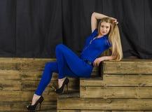 Die schöne Blondine mit dem langen Haar im blauen Overall und den hohen Absätzen, die auf einem hölzernen Treppenhaus liegen Stockbilder