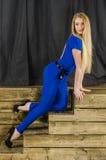 Die schöne Blondine mit dem langen Haar im blauen Overall und den hohen Absätzen, die auf einem hölzernen Treppenhaus liegen Stockbild