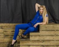 Die schöne Blondine mit dem langen Haar im blauen Overall und den hohen Absätzen, die auf einem hölzernen Treppenhaus liegen Stockfotos