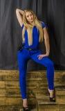 Die schöne Blondine mit dem langen Haar im blauen Overall und den hohen Absätzen, die auf einem hölzernen Treppenhaus liegen Stockfoto