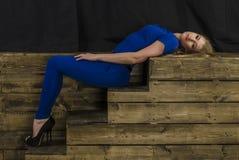 Die schöne Blondine mit dem langen Haar im blauen Overall und den hohen Absätzen, die auf einem hölzernen Treppenhaus liegen Stockfotografie
