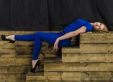 Die schöne Blondine mit dem langen Haar im blauen Overall und den hohen Absätzen, die auf einem hölzernen Treppenhaus liegen Lizenzfreie Stockfotografie