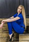 Die schöne Blondine mit dem langen Haar im blauen Overall und den hohen Absätzen, die auf einem hölzernen Treppenhaus liegen Lizenzfreie Stockfotos
