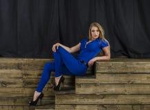 Die schöne Blondine mit dem langen Haar im blauen Overall und den hohen Absätzen, die auf einem hölzernen Treppenhaus liegen Lizenzfreies Stockfoto