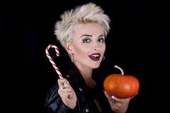 Die schöne Blondine mit einem Kürbis und einer Süßigkeit in den Händen Stockbilder