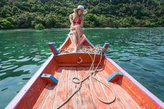 Die schöne Blondine sitzt auf dem Bogen von hölzernen Booten und bewundert das Meer Lizenzfreie Stockbilder