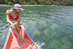 Die schöne Blondine sitzt auf dem Bogen von hölzernen Booten und bewundert das Meer Stockbild