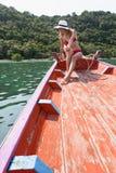 Die schöne Blondine sitzt auf dem Bogen von hölzernen Booten und bewundert das Meer Lizenzfreie Stockfotos