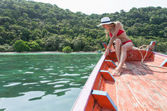 Die schöne Blondine sitzt auf dem Bogen von hölzernen Booten und bewundert das Meer Lizenzfreies Stockfoto