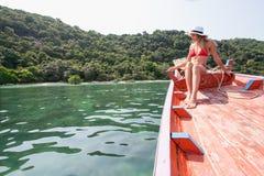 Die schöne Blondine sitzt auf dem Bogen von hölzernen Booten und bewundert das Meer Stockfoto