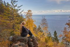Die schöne Blondine sitzt auf dem Felsen mit einem Hund und bewundert eine Ansicht des Herbstsees Stockfotografie