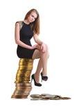 Die schöne Blondine sitzt auf einer Spalte von Münzen Lizenzfreie Stockfotografie