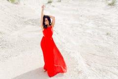 Die schöne brunette junge Frau, die im langen roten Kleid gekleidet wird, wirft auf Sand in der Wildnis, äußeres Schießen auf stockfotos