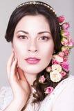 Die schöne Brunettebraut, die mit natürlichem lächelt, bilden und blühen Rosen in ihrer Frisur Stockfoto