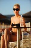 Die schöne Frau, die in einem Strandstab mit a sitzt lizenzfreie stockbilder