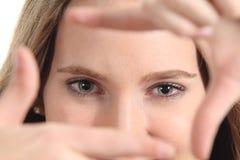 Schöne Frau, die ihre blauen Augen mit den Fingern gestaltet Stockfotos