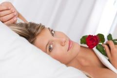 Die schöne Frau, die im Bett anhält Rot liegt, stieg Stockbild