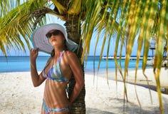 Die schöne Frau, die unter Palme steht, verzweigt sich auf den Hintergrund der Karibischen Meere Stockfoto
