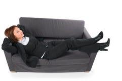 Die schöne Geschäftsfrau, die auf einem Sofa liegt lizenzfreie stockfotos