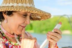 Die schöne Greisin, einen Strohhut tragend untersucht ihr smartph Lizenzfreie Stockbilder