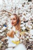 Die schöne junge blonde Frau, die mit Magnolie umgeben wird, blüht im Frühjahr Garten Lizenzfreie Stockfotos