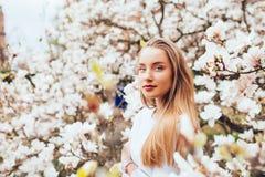 Die schöne junge blonde Frau, die mit Magnolie umgeben wird, blüht im Frühjahr Garten Lizenzfreies Stockbild