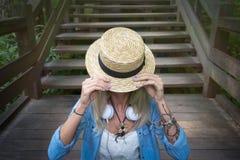 Die schöne junge blonde Hippie-Frau, die auf der hölzernen Treppe sitzt, schließt das Strohhut ` s Gesicht Die Frau wird in a gek Lizenzfreies Stockfoto