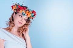 Die schöne junge Frau, die Blumenstirnbandtiarakrone trägt, lokalisierte hellblauen Hintergrund mit farbigen Blumen auf Kopf lizenzfreie stockbilder