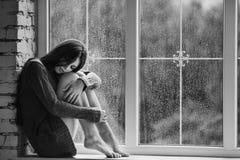 Die schöne junge Frau, die allein nah an Fenster mit Regen sitzt, fällt und trauriges Mädchen Konzept der Einsamkeit schwarz Lizenzfreies Stockfoto