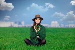 Die schöne junge Frau, die auf dem Gras mit Herzen sitzt, formte Spielzeug Stockbilder