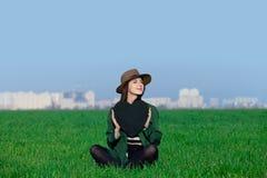Die schöne junge Frau, die auf dem Gras mit Herzen sitzt, formte Spielzeug Stockbild