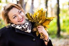Die schöne junge Frau, die Blätter im Herbst lächelt und hält, parken Stockfotografie