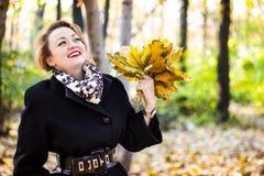 Die schöne junge Frau, die Blätter im Herbst lächelt und hält, parken Stockbild