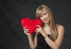 Die schöne junge Frau, die ein Herz hält, formte Rot Stockbild