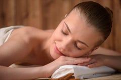 Die schöne junge Frau, die entspannend erhält, ist Badekurort Lizenzfreie Stockfotografie