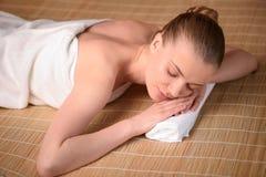 Die schöne junge Frau, die entspannend erhält, ist Badekurort Stockfoto