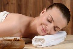 Die schöne junge Frau, die entspannend erhält, ist Badekurort Stockfotografie