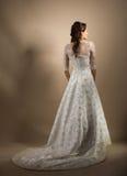 Die schöne junge Frau in einem Hochzeitskleid Lizenzfreie Stockfotografie