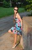 Die schöne junge Frau kostet auf Allee im Sommerpark Lizenzfreies Stockfoto
