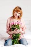 Die schöne junge Frau mit Verband der Rosen Stockfoto