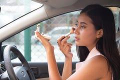 Die schöne junge Frau sitzen im Auto auf dem Fahrersitz, der Rückspiegel überprüfend betrachtet und bürsten bilden Asiatisches Mä stockbild